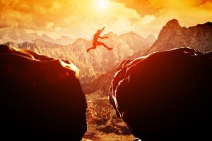 homem pulando precipício risco