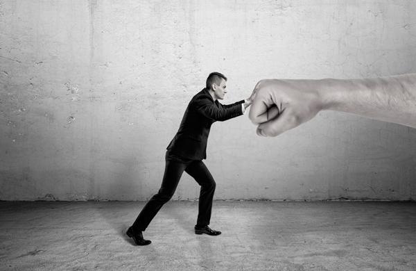 Taxa Referencial - um homem tentando segurar um braço gigante com as mãos