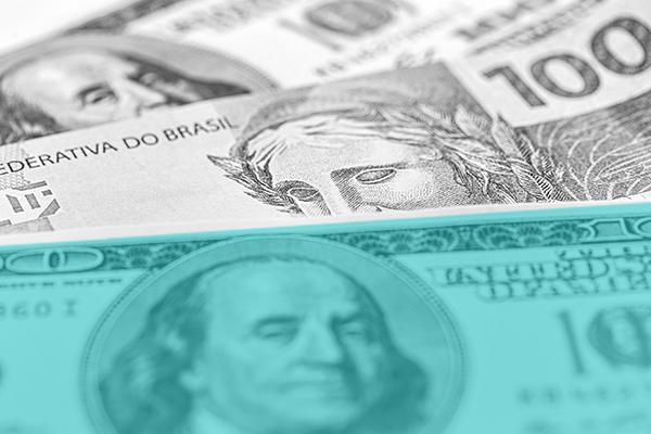 Dólar vs Real - as duas notas em destaque com o dólar em verde enquanto o real está em cinza