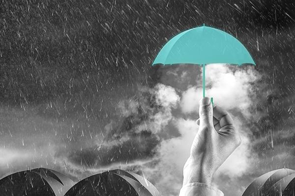 seguro de vida: uma mão segurando um guarda-chuva
