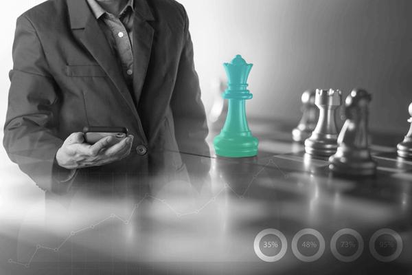 Carteira Administrada, uma peça de xadrez em destaque enquanto uma pessoa olha para o celular no fundo, representando estratégia de investimento.