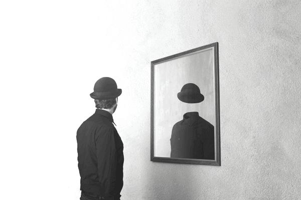 Consultor CVM: Um homem olhando no espelho e no reflexo está apenas suas roupas e chapéu, seu rosto está vazio