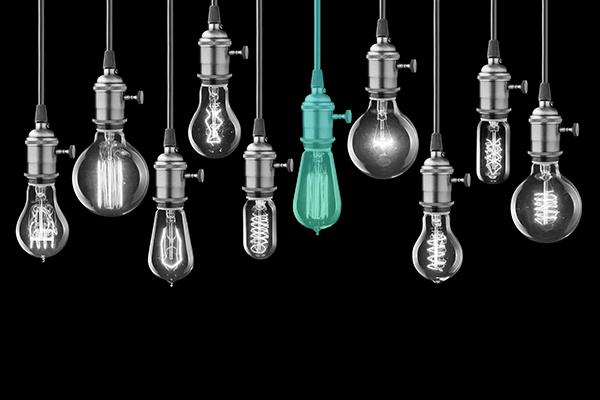 fundos de investimento: diversas lâmpadas em preto e branco, enquanto existe uma central colorida em verde