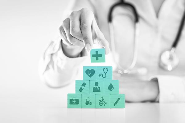 o que é seguro saúde? -Um médico empilhando diversos blocos com símbolos que representam a medicina